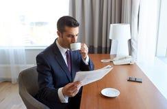 Läs- tidning för affärsman och drickakaffe Royaltyfri Bild