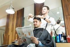 Läs- tidning för kund medan Barber Cutting His Hair royaltyfri bild