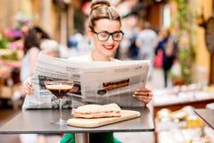 Läs- tidning för kvinna på kafét utomhus Arkivbild