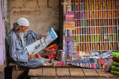 Läs- tidning för lokal man på gatamarknaden i Fatehpur Sik Arkivfoton