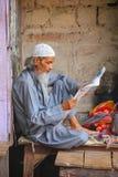 Läs- tidning för lokal man på gatamarknaden i Fatehpur Sik Arkivbilder