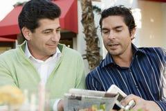 Läs- tidning för manar på cafen Royaltyfri Bild