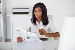 Läs- tidning för nätt affärskvinna på hennes skrivbord Arkivfoton
