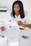 Läs- tidning för nätt affärskvinna på hennes skrivbord Royaltyfria Bilder