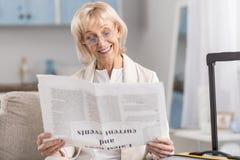 Läs- tidning för optimistisk mogen kvinna royaltyfri bild