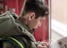 Läs- tidning för tonårig pojke Arkivbild