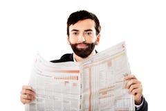 Läs- tidning för ung man i kontoret Arkivbild