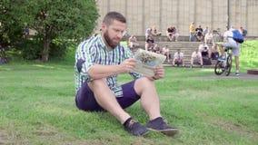 Läs- tidning för ung man, sammanträde på gräs steadicam arkivfilmer