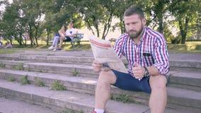 Läs- tidning för ung man, sammanträde på trappa stock video