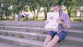 Läs- tidning för ung man, sammanträde på trappa Glidare- och pannaskott stock video