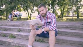 Läs- tidning för ung man, sammanträde på trappa glidareskott arkivfilmer