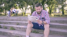 Läs- tidning för ung man, sammanträde på trappa Glidareskott som är högert lager videofilmer
