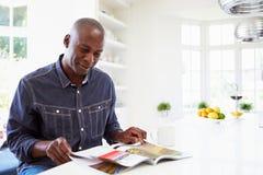 Läs- tidskrift för afrikansk amerikanman hemma royaltyfri bild