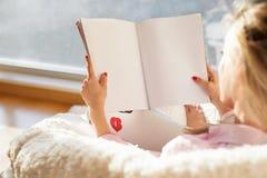 Läs- tidskrift för kvinna med tomma vita tomma sidor Modell för dina egna innehåll Royaltyfri Fotografi