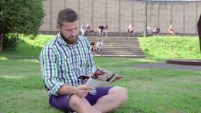 Läs- tidskrift för ung man och bläddrasmarphone som sitter på gräs lager videofilmer