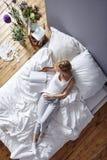 Läs- tidskrift i säng arkivfoto