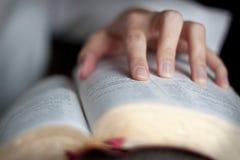 Läsa en bibel med en hand på bibeln Royaltyfri Foto