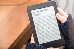 Läsa en bok med en eBookavläsare Royaltyfria Bilder