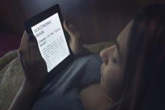 Läsa en ebook i säng Royaltyfri Bild