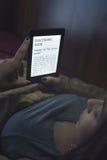 Läsa en ebook i säng Royaltyfri Fotografi