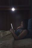 Läsa en ebook i säng Royaltyfria Foton