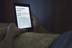 Läsa en ebook i säng Royaltyfri Foto