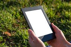 Läsa en ebook på en minnestavla i parkera Royaltyfria Bilder
