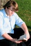 läsa för pojke som utomhus är teen Royaltyfri Foto