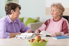 Läsa för två äldre kvinnor royaltyfria bilder