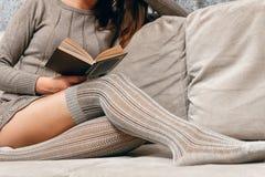 Läsa, medan sitta på soffan royaltyfri bild