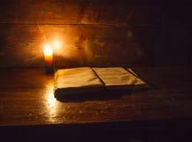 Läsa plats i forntida tider: en gammal bok som lutar på den förstörda trätabellen som tänds av en stearinljus på en träbakgrund arkivbilder