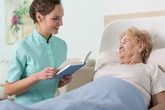Läsa till äldre kvinna Arkivbild