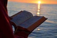 Läsa under solnedgång på Östersjön royaltyfria foton