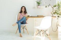 Läsa utbildning, kultur, folkbegrepp - den unga studentkvinnan läser en bok, medan hon sitter på vit stol royaltyfri foto