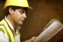 Läsande arkitektoniska industriella plan för manlig byggmästareplatsordförande arkivfoto