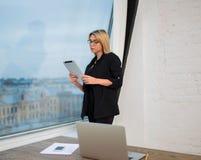 Läsande finansiell nyheterna för kvinnlig stolt vd i internet via det bärbara handlagblocket Royaltyfri Foto