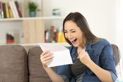Läsande stor nyheterna för upphetsad kvinna i en bokstav royaltyfri bild
