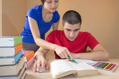 Läseböcker för äldre broder och studentsyster på skrivbordet i vardagsrum Royaltyfri Foto