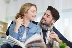 Läseböcker för ung man och kvinnapå soffan fotografering för bildbyråer