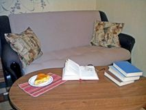Läseböcker med en smaklig paj på soffan arkivfoton