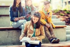 Läsebok för högstadiumstudentflicka utomhus arkivbilder