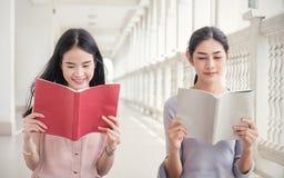 Läsebok för två asiatisk flickor tillsammans books isolerat gammalt för begrepp utbildning Arkivfoto