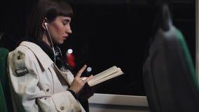 Läsebok för ung kvinna eller passagerareoch att lyssna musik som offentligt sitter transport, steadicamskott l?ngsam r?relse Stad arkivfilmer