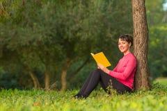 Läsebok för ung kvinna i parkera Arkivfoto