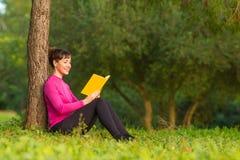 Läsebok för ung kvinna i parkera Arkivbild
