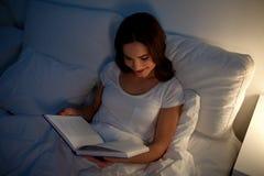 Läsebok för ung kvinna i säng på natthemmet Fotografering för Bildbyråer