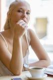 Läsebok för ung kvinna på kafét Royaltyfri Bild
