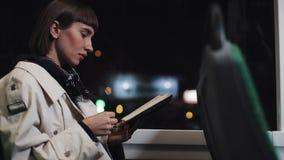 Läsebok för ung kvinna som eller passagerareoffentligt sitter transport, steadicamskott l?ngsam r?relse Staden t?nder bakgrund stock video