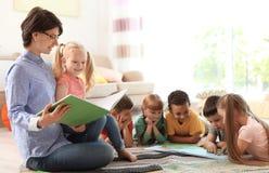 Läsebok för ung kvinna till små barn inomhus fotografering för bildbyråer
