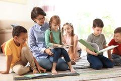 Läsebok för ung kvinna till små barn inomhus arkivfoton